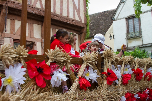 Children participating in floats decorated with wheat and flowers at the Harvest Festival in Provins