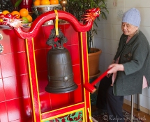 Temple guardian sounding the gong for each visitors entering the chapel