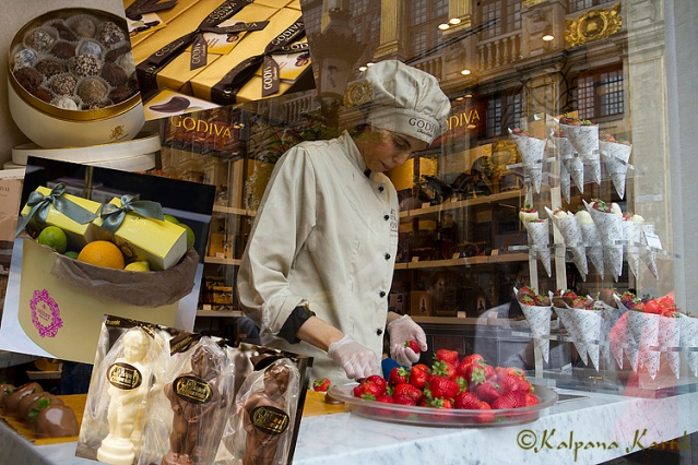 Dipping fresh strawberries in chocolate at Godiva chocolate.  Boxes of famous Belgian chocolates, Meert, La Belgique Gourmande, Godiva and Mary