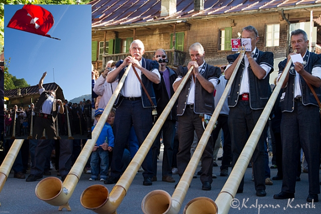 Alphorn players and flag throwers perform during the cattle descent festival in the mountain village of Charmey